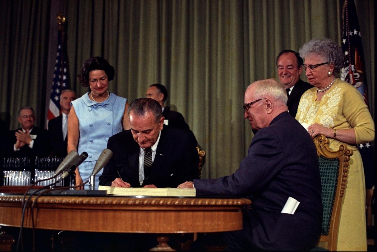 Lyndon_Johnson_signing_Medicare_bill_with_Harry_Truman_July_30_1965.jpg
